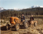 Roxy Pomeroy pulling Harold Pomeroy in a tractor at Bear Cove.
