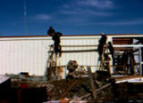 People working on exterior of fish plant building in Unalakleet.