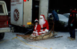 Santa and female helper sit in Joe Redington Sr.'s dog sled.