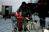 Joe Redington Sr. poses with two children next to sled dogs.