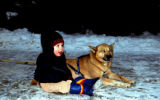 Child sits in snow next to sled dog named Tang.