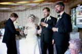 Bride Kathy Walker poses with groom with two men wearing suits.