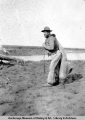 Lee Wise with baby beluga on Theodore Creek, 1919.