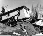 A car smashed under a house in the 1964 earthquake, Turnagain area, Anchorage.