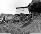 A man recovers some possessions after the 1964 earthquake, Turnagain area, Anchorage.