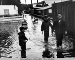 Three boys and some dogs walk in the flooded town of Seldovia after the 1964 earthquake.