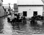 Men distributing sandbags in flooded Seldovia after the 1964 earthquake.