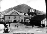Wharf at Sitka, Alaska, showing Barinoff [sic] Castle Hill with modern house on it.