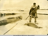 Eskimo hunter with kayak and a seal.
