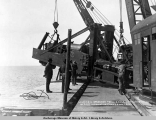 Landing a spreader from barge Lawrence by A.E.C. locomotive cranes no's. 1 & 2.