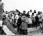 Eskimos watching cornerstone laying at Federal Building. Nome, Alaska.
