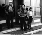Hoonah. Three fishermen in front of Kane's Store, dispensers of groceries and liquors. 1938.