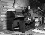 Mrs. Atwood at organ at her home in Turnagain.