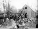 Erecting power plant to furnish power during the construction of Susitna River bridge.