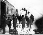 Passengers from Anchorage walking over snow at slide, mile 72, Gov't R[ail]road, to take train for...