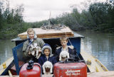 Vi, Tim, and Raymie Redington in a boat with four puppies on Fish Creek at Flathorn Lake.