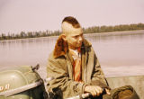 Joe Redington Jr. with mohawk hairdo, steering boat.
