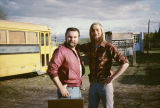 Bill Devine and Jeff Schultz in front of a yellow bus.