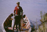Tim Redington standing in a boat holding two king salmon.