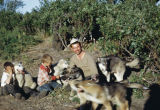 Joe Redington Jr., Raymie Redington, and Joe Redington Sr. playing with pups at mouth of Susitna...