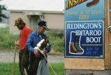 Duane Lambert, Joe Redington Sr., and one sled dog in front of a sign advertising Redington's...