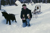 Raymie Redington with lead dog Tippy, holding race trophies.
