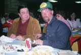 Joe Redington Jr. and another man eating at an All Alaska Sweepstakes event.