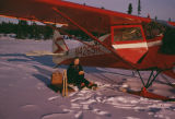 Vi Redington sitting in front of Joe Redington Sr.'s plane.