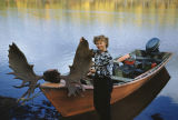 Vi Redington on shore with a boat with moose antlers on the front.