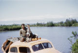 Joe Redington Sr. with wheel dog Chinook sitting on top of the boat.