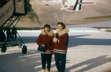 Two stewardesses for Alaska Airlines stand in front of airplane in winter, wearing parkas with fur...