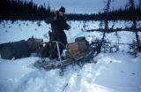 GI on trail beside dog sled during Army maneuvers.