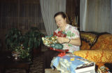 Vi Redington unwrapping a Christmas gift.