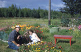 Sharon and Florence Fleckenstein sitting in a flower bed.