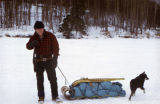 Man pulling a toboggan sled loaded with gear and snowshoes, with loose sled dog pup.