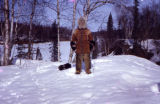 Joe Redington Sr. poses with fur coat at the Flat Horn homestead.