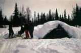 People wearing snowshoes, camping in a snow-covered shelter.