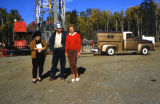 Dorothy Page and two people posing in front of heavy machinery, possibly a drilling rig.
