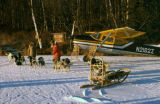 Dog team, snowshoes, and people posed in front of airplane for publicity photo shoot on Knik Lake.