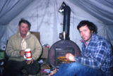 Joe Redington Sr. with man sitting inside a tent next to a wood stove.