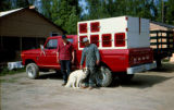 Two men with dog truck.