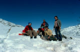 Joe Redington, Sr., and two three women rest on sled.