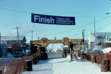 End of the 1975 Iditarod Trail Sled Dog Race with banner and burled arch.