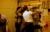 Iditarod race volunteers spray painting race bibs inside garage.