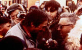 Dick Mackey interviewed by Orville Lake, crowds onlooking, after Mackey won the 1978 Iditarod...