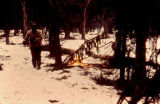 Herbie Nayokpuk drying harnesses above a campfire on the 1973 Iditarod Trail Sled Dog Race.