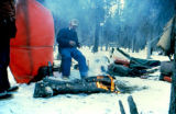 Jim Strong camping along the Iditarod Trail with dog sled in the background.