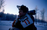 Musher with race bib and gear on the Iditarod Trail Sled Dog Race.