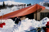 Man in front of winter tent on Joe Redington Sr.'s Iditarod Challenge.