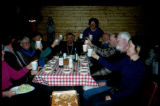 Participants in Joe Redington Sr.'s 1995 Iditarod Challenge seated for a meal during the trip.